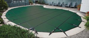 Green safety cover on inground pool